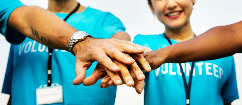 Volunteers putting their hands together in a pile.