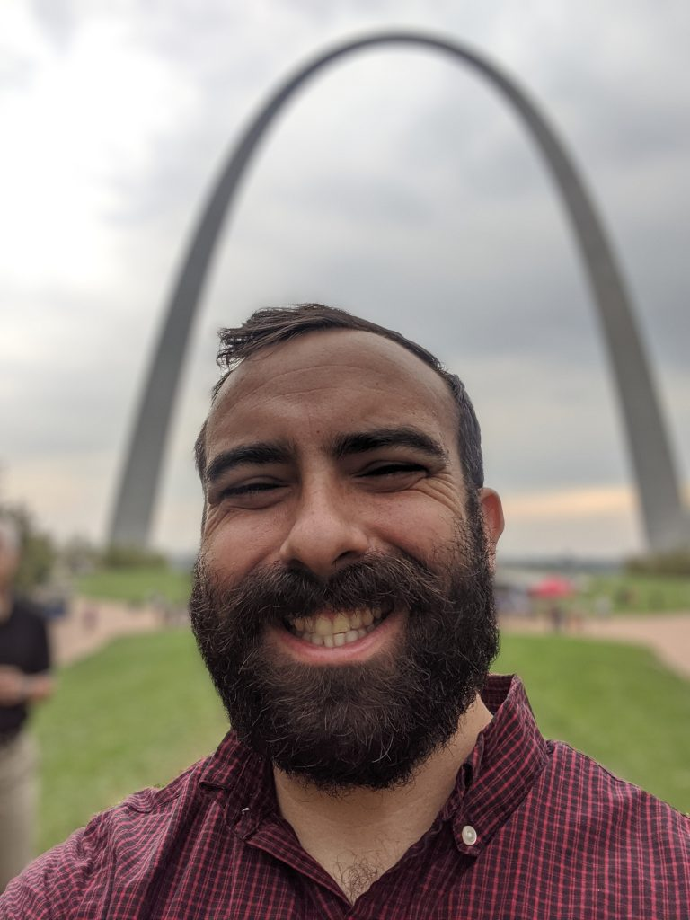 Director of Campaigns & Advocacy smiles in front of the St. Louis Arch.