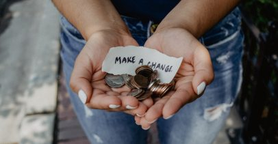 "Hands holding coins and a note that says ""Make a change"""