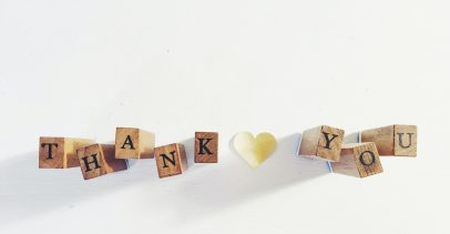 """Thank You"" spelled out with wooden blocks and a paper heart between the two words."