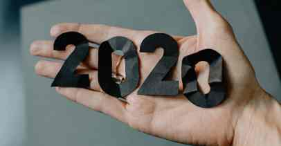 "A hand is shown, palm facing up, holding black cut out numbers that spell ""2020"""