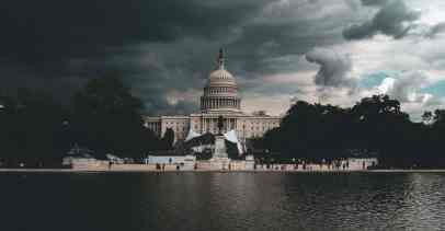The US Capitol is seen from the Reflecting Pool, with dark clouds behind it